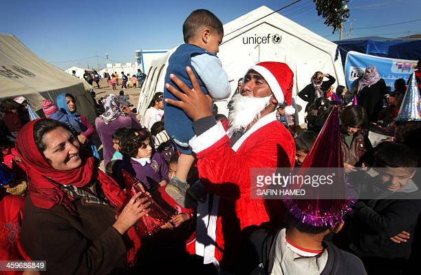 A SyrianKurdish refugee man dressed in Santa Claus carries a child during Christmas celebrations in the Quru Gusik refugee camp 20 kilometers east of...