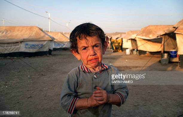 A SyrianKurdish refugee poses at sunset in an alley of the Quru Gusik refugee camp 20 kilometres east of Arbil the capital of the autonomous Kurdish...