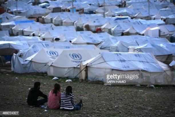 SyrianKurdish refugees sit and look on at the Quru Gusik refugee camp 20 kilometres east of Arbil the capital of the autonomous Kurdish region of...