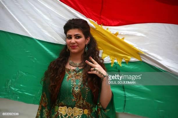 A SyrianKurdish woman modelling traditional Kurdish attire poses in front of a Kurdish flag during a fashion show in the northeastern Syrian city of...