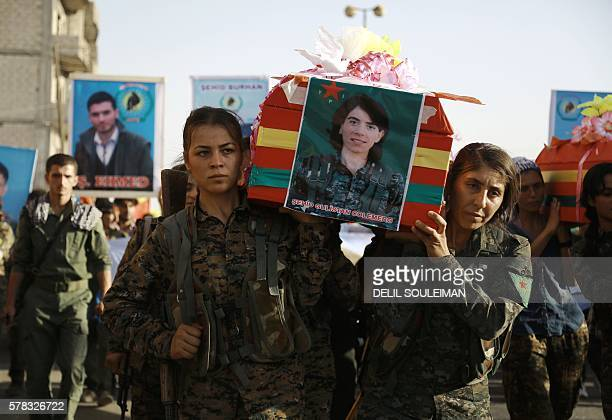 SyrianKurdish women carry the coffin of a female fighter in Syria's northeastern city of Qamishli on July 21 2016 during the funeral of sixteen...