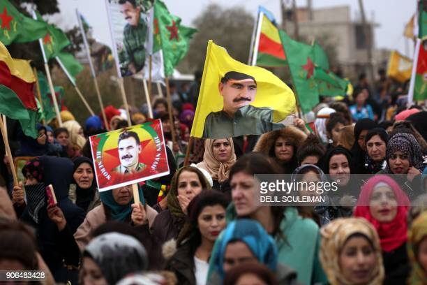 TOPSHOT SyrianKurds carry portraits depicting jailed founding member and leader of the Kurdistan Worker's Party Abdullah Ocalan as they march during...