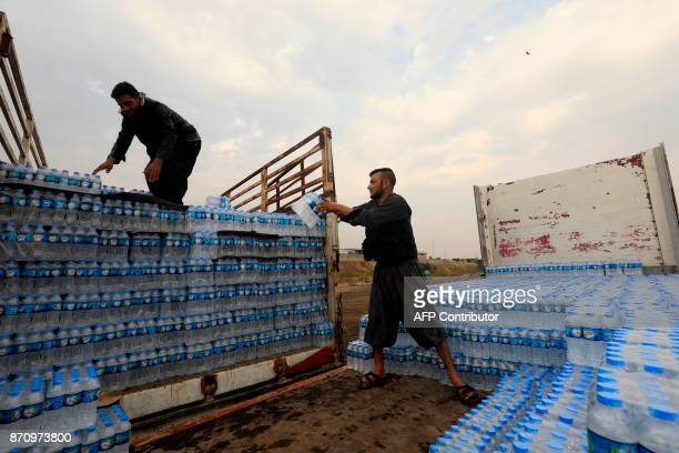 SyrianKurds load water bottles onto a truck before being transported from Syria's northeastern Kurdish area into Iraq across the Tigris river just...