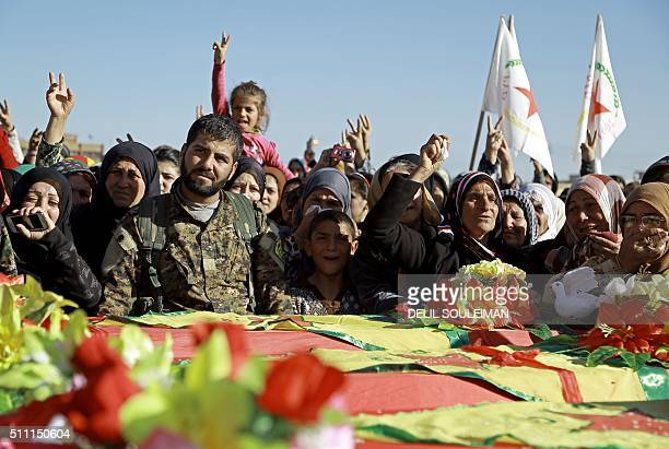 SyrianKurds mourn next to coffins as they attend the funeral procession of four Kurdish fighters in the northeastern Syrian city of Qamishli on...
