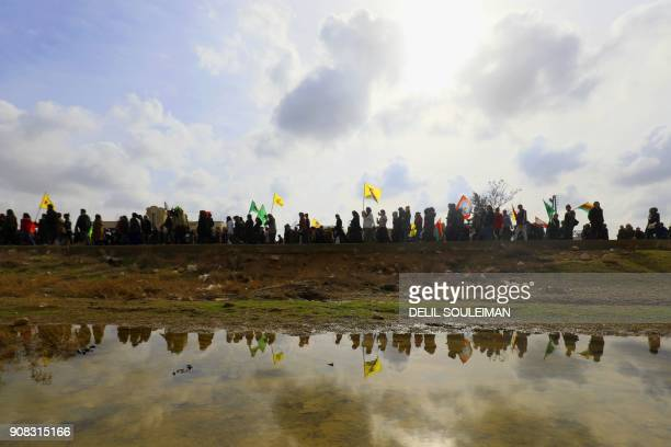 TOPSHOT SyrianKurds take part in a demonstration in the town of Amuda some 30 kilometres west of Qamishli a Kurdishmajority city in northeastern...
