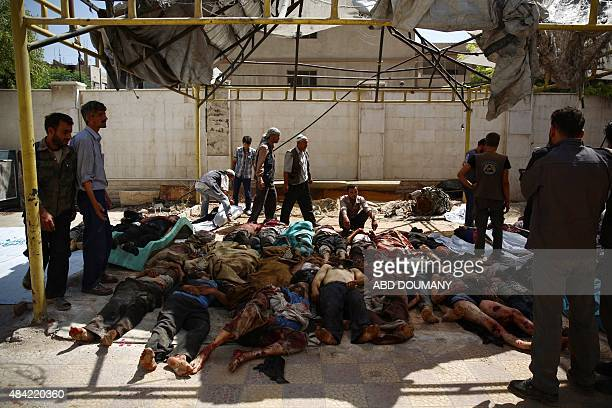 Syrians and emergency personnel gather around bodies following air strikes by Syrian government forces on a marketplace in the rebelheld area of...