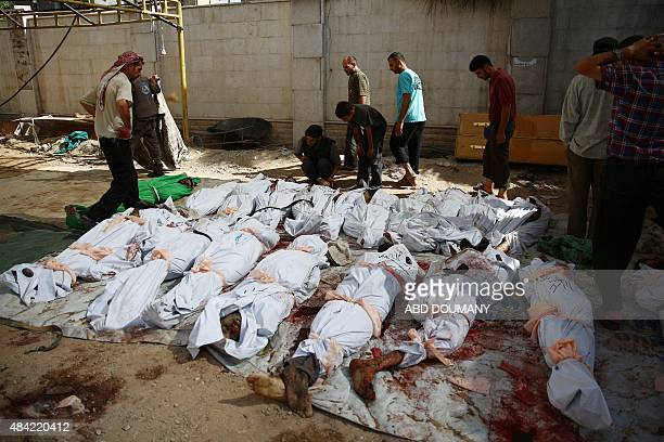 Syrians and emergency personnel gather around dead bodies wrapped in shrouds following air strikes by Syrian government forces on a marketplace in...