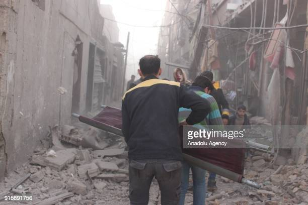 Syrians and members of NGOs conduct a search and rescue operation amid destroyed buildings after Assad Regime carried out an airstrike over Douma...