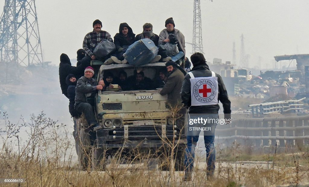TOPSHOT - Syrians are evacuated from a rebel-held area of Aleppo towards rebel-held territory in the west of Aleppo's province on December 16, 2016. Russia announced it was negotiating with the Syrian opposition and seeking a nationwide ceasefire, as the evacuation of civilians and fighters from the last rebel-held parts of Aleppo entered a second day. The Syrian Observatory for Human Rights, a Britain-based monitor of the war, estimated some 8,500 people had left so far, including around 3,000 rebel fighters. Syrian state media reported a figure of around 8,000. / AFP / STRINGER