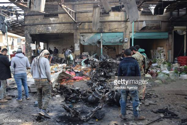 Syrians are seen at the scene after a car bombing targeted a marketplace in Afrin Syria on December 16 2018 At least four people were killed and...