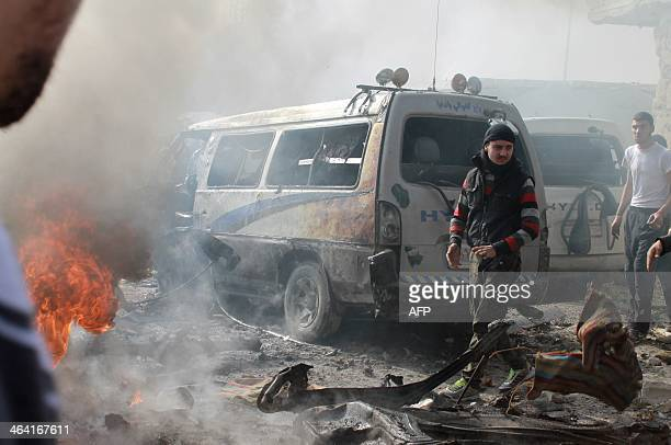 Syrians are seen at the scene of a reported airstrike by government forces on the central alFardous neighbourhood of the northern Syrian city of...