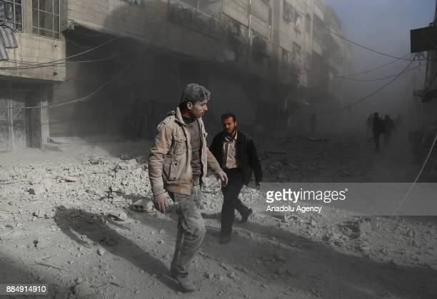 Syrians are seen on wreckage of collapsed buildings following the Assad regime's air strikes over residential areas in the deescalation zone in the...