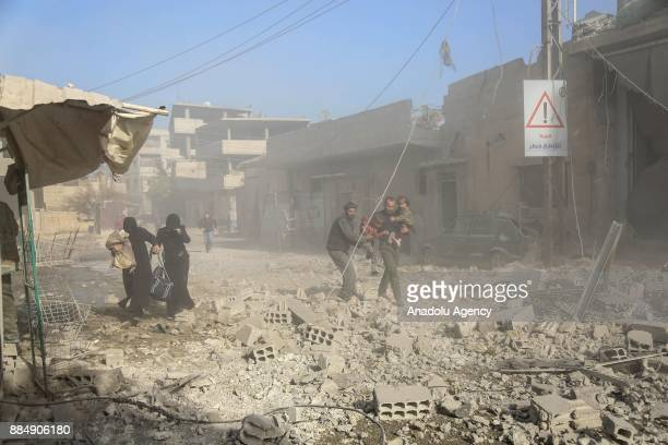 Syrians are seen through following the Assad regime's air strikes over residential areas in the deescalation zone in the Eastern Ghouta region in...