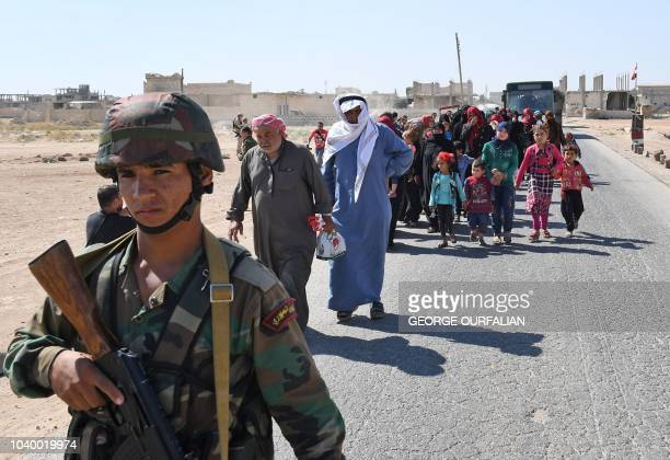Syrians arrive at the Abu Duhur crossing on the eastern edge of Idlib province on September 25 as they cross from rebelheld areas to regimeheld areas...