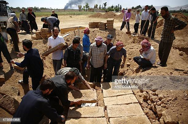 Syrians burry relatives and friends who died during the ongoing fighting between rebel fighters and Syrian regime forces on May 16 2015 at a cemetery...