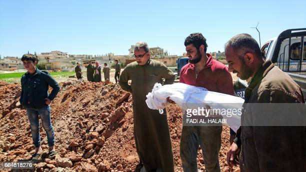 Syrians bury the bodies of victims of a a suspected toxic gas attack in Khan Sheikhun a nearby rebelheld town in Syrias northwestern Idlib province...