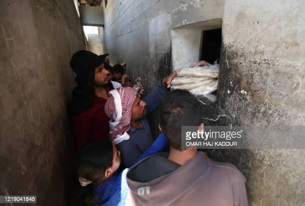 Syrians buy bread at a shop in the town of Binnish in the country's northwestern Idlib province on June 9, 2020. - Syrians held a third day of rare...