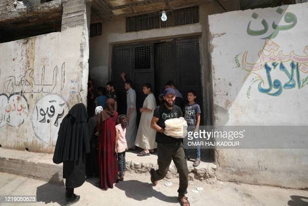 Syrians buy bread in the town of Binnish in the country's northwestern Idlib province on June 9, 2020. - Syrians held a third day of rare anti-regime...