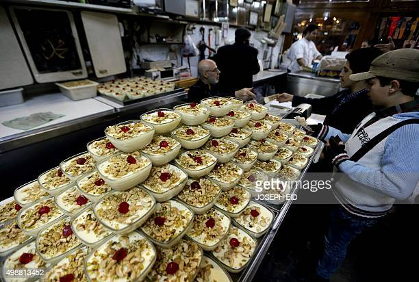 Syrians buy traditional ' Mhalabiyeh' sweets and icecream at the famous 'Bagdash' sweet shop in the Hamidiyeh popular market in the old part of the...