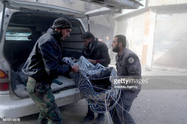 Syrians carry a dead body following the Assad regime's air strikes over residential areas in the deescalation zone in the Eastern Ghouta region in...