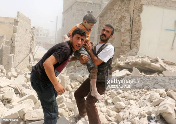 Syrians carry a wounded child in the rubble of buildings following a barrel bomb attack on the Bab alNairab neighbourhood of the northern Syrian city...