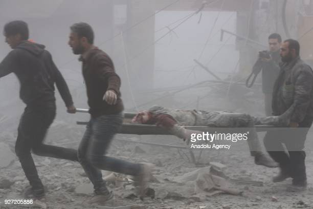 Syrians carry a wounded man after Assad Regime's airstrike hit residential areas in Eastern Ghouta's Douma town despite decisions to implement a...