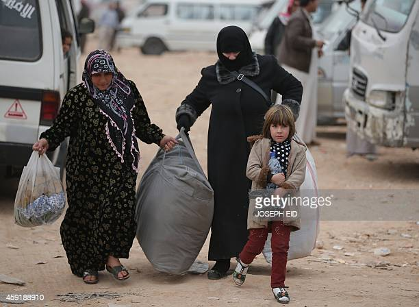 Syrians carry belongings a bus station at the AlMuhandiseen roundabout in the New Aleppo district of the northern Syrian city on November 16 2014...