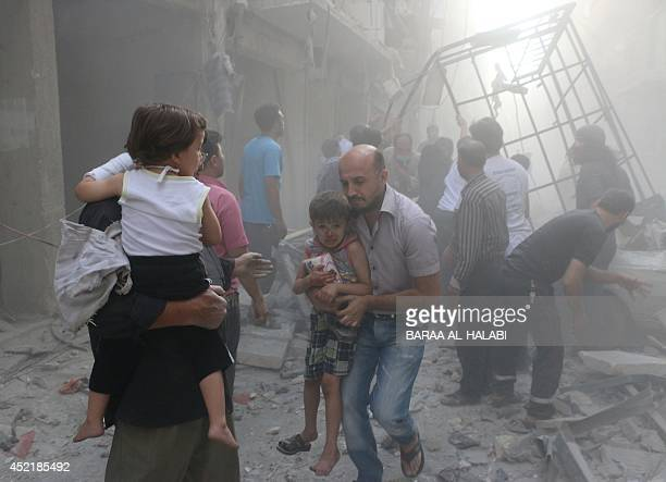 Syrians carry children amid debris following a air strike by government forces in the northern city of Aleppo on July 15 2014 More than 170000 people...