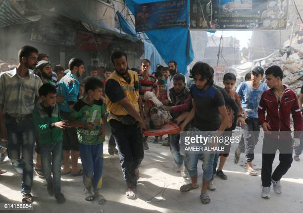 TOPSHOT Syrians carry the body of a man following air strikes on the rebelheld Fardous neighbourhood of the northern embattled Syrian city of Aleppo...