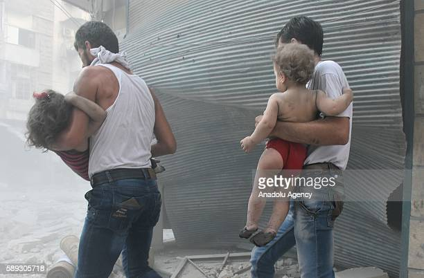 Syrians carry their children after war crafts belonging to the Syrian army carried out airstrikes at Bustan alQasr district of Aleppo Syria on August...