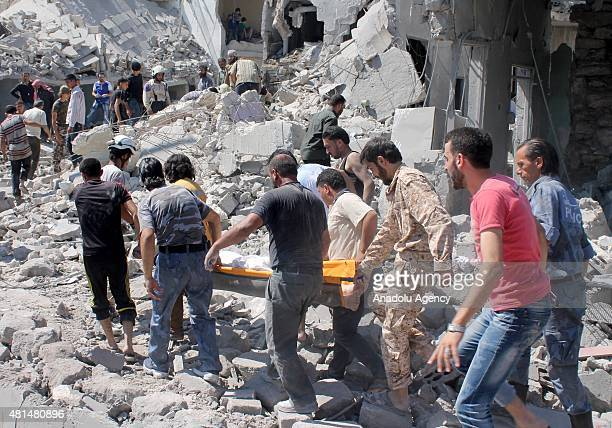 Syrians carry wounded ones to hospitals after Assad regime forces hit the oppositioncontrolled Al Magair neighbourhood of Aleppo Syria on July 21 2015