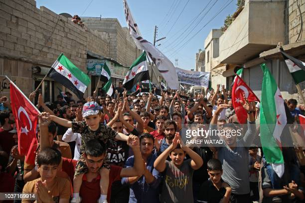 Syrians chant slogans as they wave flags of the opposition and of Turkey during a demonstration against the Syrian government in the rebelheld town...