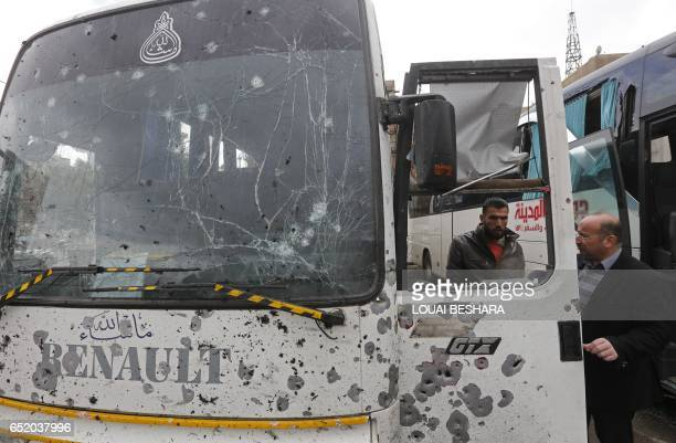 Syrians check a damaged bus at the scene of a bombing following twin attacks targeting Shiite pilgrims in Damascus' Old City on March 11 2017 A...