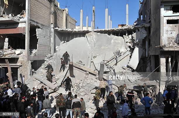 TOPSHOT Syrians check the rubble at the site of two car bomb attacks in the alZahraa neighbourhood of the central Syrian city of Homs on December 28...
