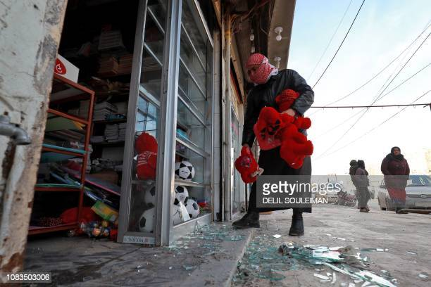 Syrians check the site of a suicide attack targeting USled coalition forces in the flashpoint northern Syrian city of Manbij which killed four US...