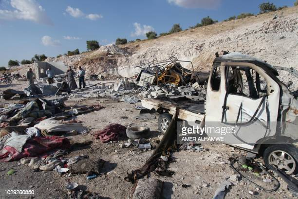 Syrians check the wreckage of a vehicle and personal belongings at a site in Hass town after an airstrike by proregime forces on the south of Idlib...