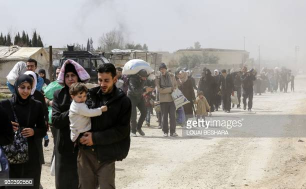 Syrians civilians evacuated from the Eastern Ghouta enclave pass with belongings through the regime-controlled corridor opened by government forces...