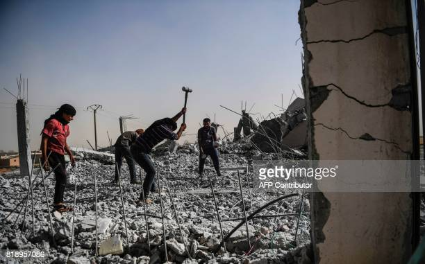 TOPSHOT Syrians clear up the rubble of their houses that were destroyed during clashes on the outskirts of Raqa on July 19 as Syrian Democratic...