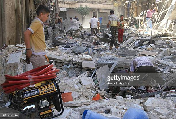 Syrians collect the remains of their houses destroyed in a Syrian government air strike in Aleppo, Syria, on June 26, 2014. At least 17 people...