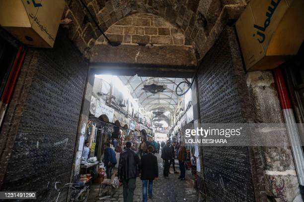 Syrians commute through Bab Al-Faraj , one of the capital city's historic gates in Damascus' old town, on March 2, 2021.