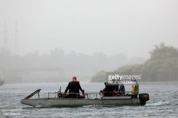 Syrians cross the Euphrates river from the city of Raqa to the countryside villages south of the city on ferries on October 15 due to the destruction...