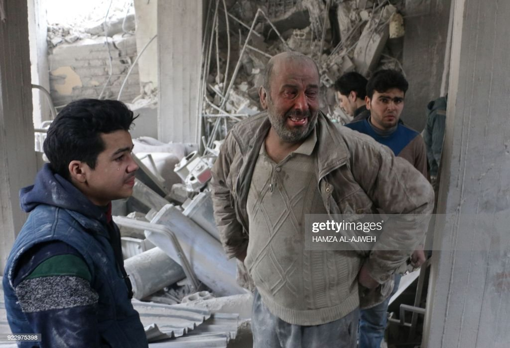 Syrians cry as they look for survivors at the site of Syrian government bombardments in Douma, in the besieged Eastern Ghouta region on the outskirts of the capital Damascus on February 22, 2018. The Syrian regime rained rockets and bombs on Eastern Ghouta, killing several civilians as international pressure mounted to stop the carnage in the rebel-held enclave. / AFP PHOTO / Hamza AL