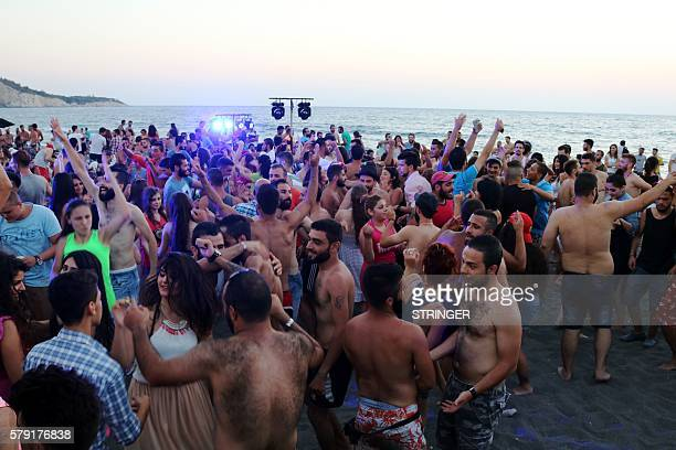 Syrians dance during a party at the Wadi Qandeel beach in the coastal city of Latakia on July 22 2016 / AFP / STRINGER
