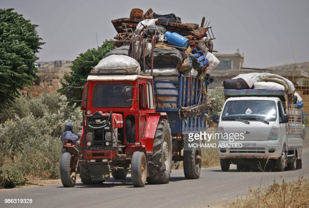 TOPSHOT Syrians displaced by government forces' bombardment in the southern Daraa province countryside ride in tractors and trucks near the town of...