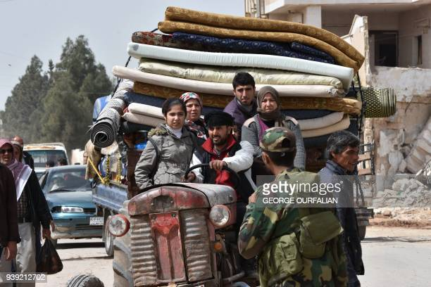 TOPSHOT Syrians displaced from the city of Afrin arrive with their belongings in the northern Syrian town of Tal Rifaat on March 28 2018 More than...