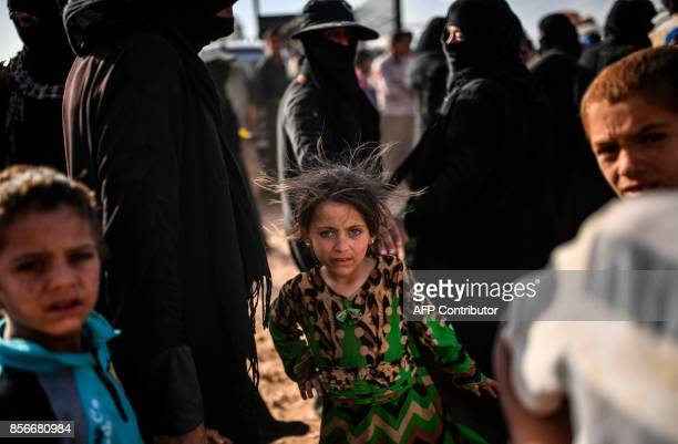 Syrians displaced from the city of Deir Ezzor wait for to get bread on the outskirts of Raqa on October 2 2017 Syrian fighters backed by US special...