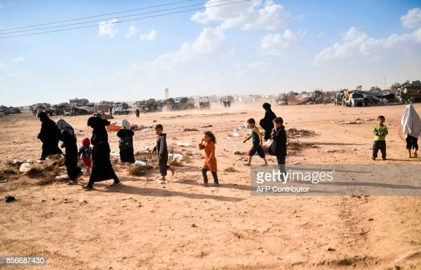 Syrians displaced from the city of Deir Ezzor walk on the outskirts of Raqa on October 2 2017 Syrian fighters backed by US special forces are...