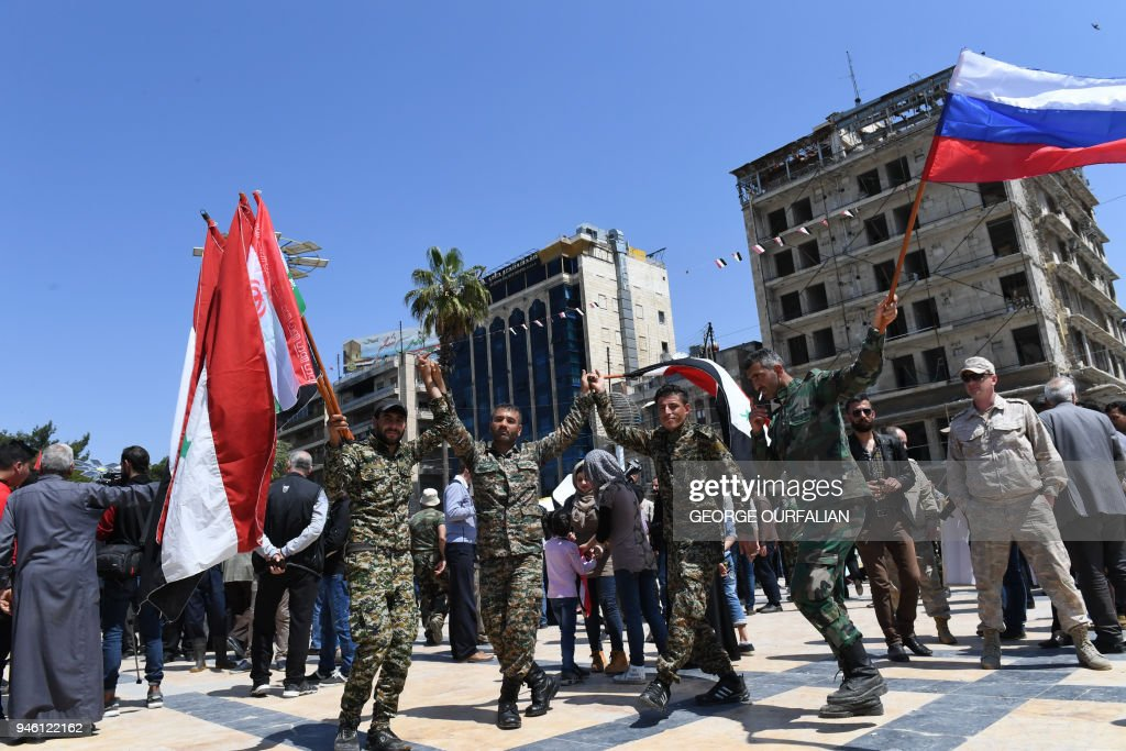 Syrians dressed in Military attire wave the Syrian and Russian flag as they gather in Aleppo's Saadallah al-Jabiri square on April 14, 2018, to condemn the strikes carried out by the United States, Britain and France against the Syrian regime. / AFP PHOTO / George OURFALIAN