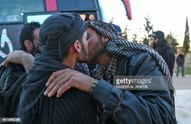 Syrians embrace following the arrival of buses carrying Jaish alIslam fighters and their families from the former rebel bastion's main town of Douma...