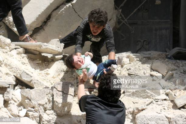 TOPSHOT Syrians evacuate a toddler from a destroyed building following a reported air strike on the rebelheld neighbourhood of alKalasa in the...